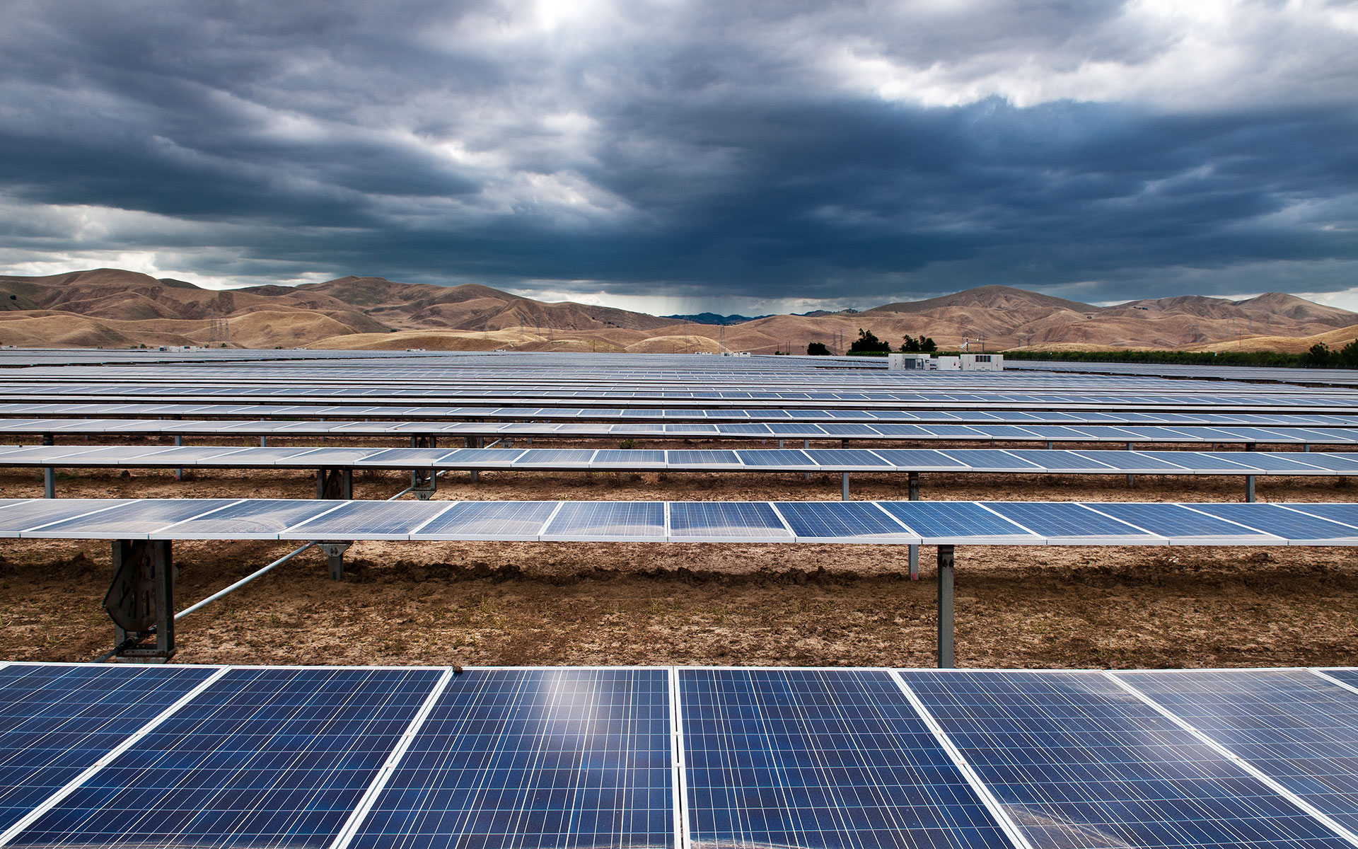 Solar panel field with cloudy sky and hills in the horizon